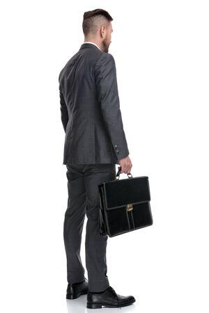 back side view of a young businessman holding a suitcase and standing on white background, he looks away from the camera