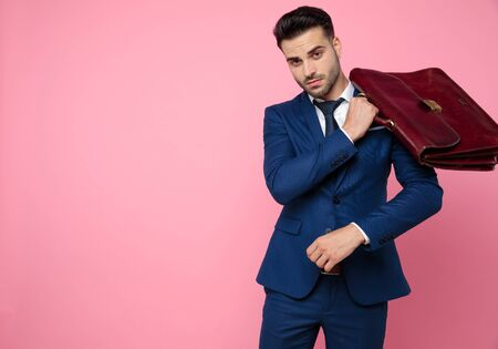 attractive young man wearing navy blue suit, holding suitcase and standing on pink background in studio