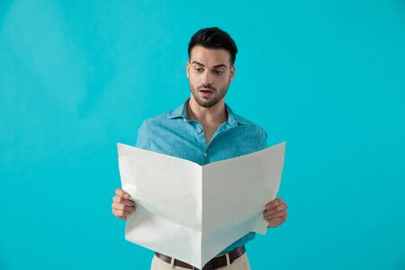 attractive casual man in blue shirt is standing and reading the newspaper shocked on blue studio background