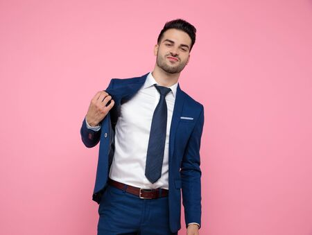 handsome young man wearing navy blue suit, holding coat and standing on pink background in studio