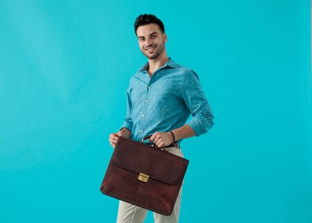young casual man with blue shirt standing with a briefcase in front of him and looking ahead happy on blue studio background
