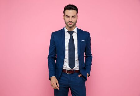 attractive young man wearing navy blue suit, holding hands in pockets, standing on pink background in studio