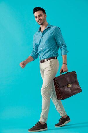 vista laterale di un bellissimo uomo casual in camicia blu che cammina e porta una valigetta con sé felice su sfondo blu studio