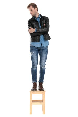 beautiful casual man with black leather jacket is standing on a wooden chair with arms crossed while looking down confident on white studio background