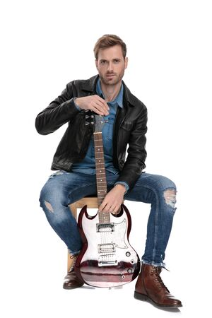 handsome casual man with black leather jacket is sitting on a wooden chair holding his guitar on white studio background