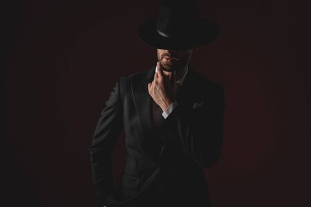 mysterious man wearing tuxedo and black hat, holding hand on chin, thinking, wondering, looking down with one hand in pocket, standing on black background, portrait