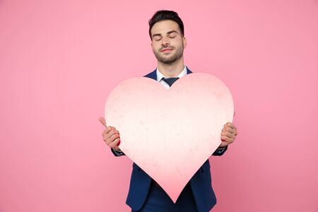 attractive young man wearing navy blue suit, holding heart, standing on pink background in studio 版權商用圖片