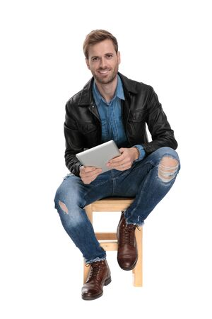 young casual man with black leather jacket is sitting on a wooden chair with a tablet on his hands happy on white studio background