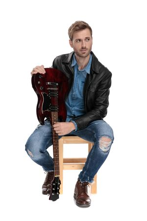 attractive casual man with black leather jacket is sitting on a wooden chair holding his guitar upside down and looking away on white studio background