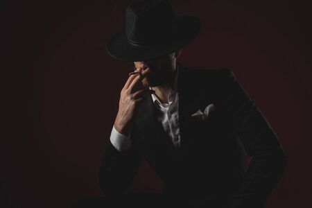 mysterious dramatic man wearing tuxedo and black hat, smoking cigarette and sitting on black background in studio