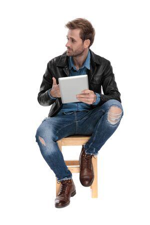 Lässiger Mann mit schwarzer Lederjacke sitzt auf einem Holzstuhl, hält ein Tablet in der Hand und schaut auf eine Seite großspurig auf weißem Studiohintergrund