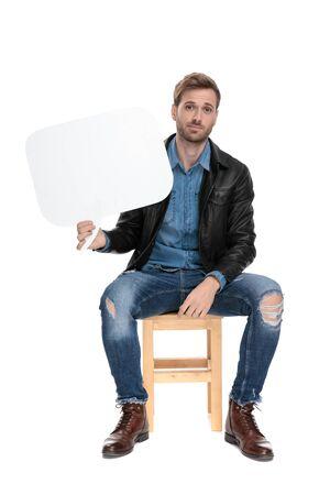 jeune homme décontracté avec une veste en cuir noir est assis sur une chaise en bois tenant une bulle de dialogue d'une part heureux sur fond de studio blanc