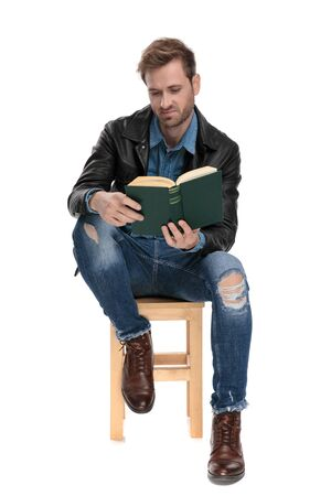 fine casual man with black leather jacket is sitting and reading a book unsatisfied on white studio background