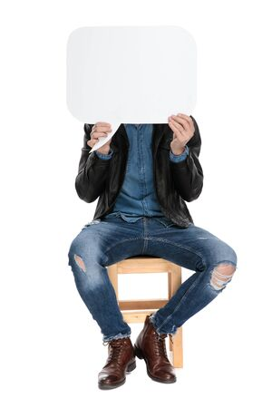 casual man with black leather jacket is sitting on a wooden chair with face covered by a speech bubble on white studio background