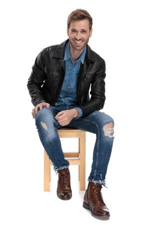 Gut aussehender lässiger Mann in schwarzer Lederjacke sitzt auf einem Holzstuhl mit den Händen auf dem Bein, während er glücklich auf weißem Studiohintergrund nach vorne schaut