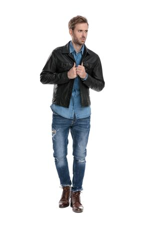 gorgeous casual man with black leather jacket is walking while fixing his jacket and looking away anxious  on white studio background
