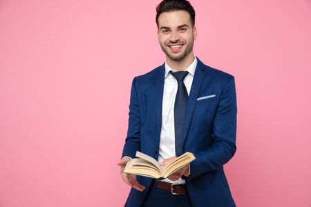 attractive young man wearing navy blue suit, holding a book and laughing, standing on pink background in studio 免版税图像