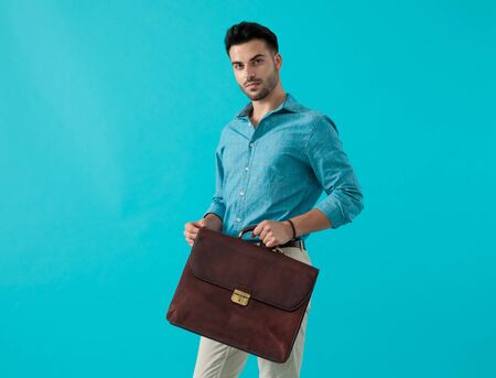 gorgeous casual man with blue shirt standing with a briefcase in front of him and looking ahead on blue studio background