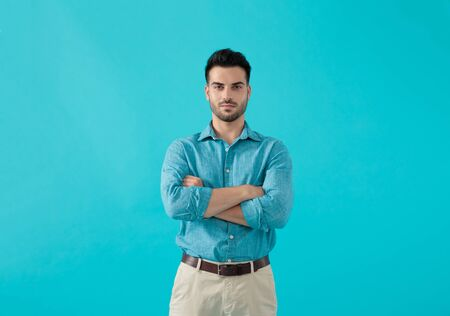 gorgeous casual man in blue shirt is standing with his arms crossed and looking ahead confident on blue studio background Stockfoto