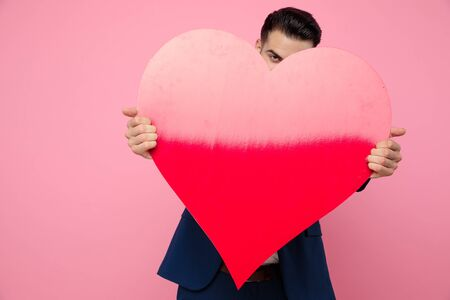 attractive young man wearing navy blue suit, holding a big heart and standing on pink background in studio Stockfoto