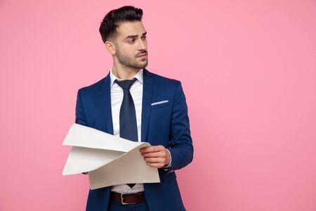 attractive young man wearing navy blue suit, holding newspaper, looking to side and standing on pink background in studio