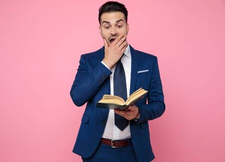 smart casual man wearing navy blue suit, reading a book and standing on pink background in studio Stockfoto