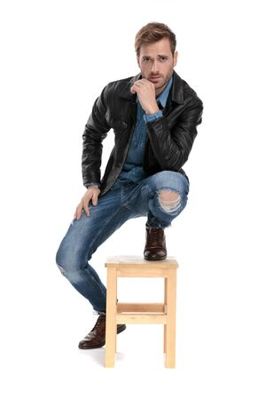sexy casual man with black leather jacket is standing with one leg down and one on chair while touching his chin on white studio background