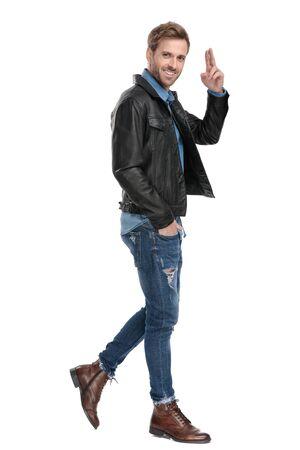Seitenansicht eines jungen lässigen Mannes mit schwarzer Lederjacke, der mit einer Hand in der Tasche geht, während er glücklich auf weißem Studiohintergrund salutiert
