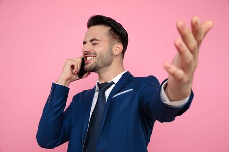 handsome young man wearing navy blue suit, talking on the phone, celebrating victory and standing on pink background in studio Stockfoto