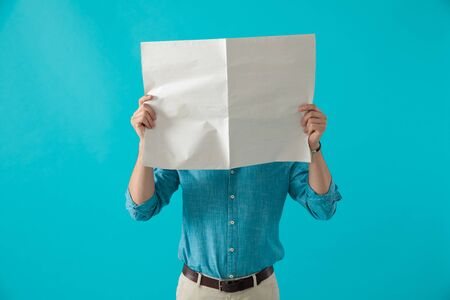 casual man in blue shirt is standing with his face covered by newspaper on blue studio background Stockfoto