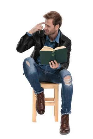 casual man with black leather jacket holding a book and imitating out of mind gesture on white studio background