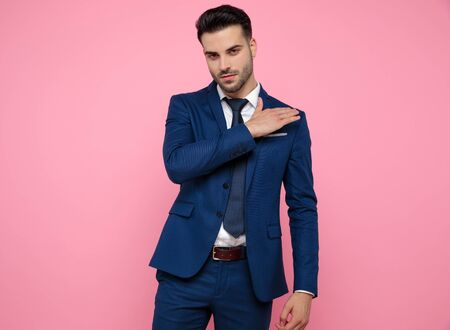 handsome young man wearing navy blue suit, touching shoulder and cleaning coat, standing on pink background in studio
