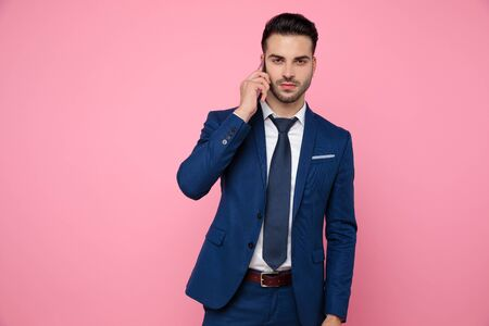 attractive young man wearing navy blue suit, talking on the phone, holding hands and standing on pink background in studio