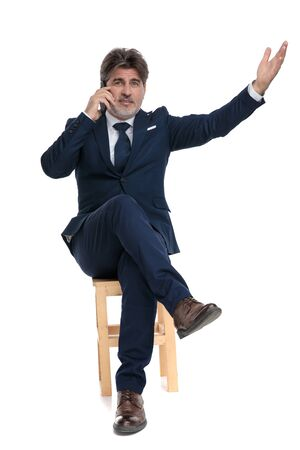gorgeous formal business man with navy suit is sitting with legs crossed talking on mobile phone and presenting to a side intrigued on white studio background