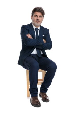sexy formal business man with navy suit is sitting with arms crossed and looking at camera confident on white studio background