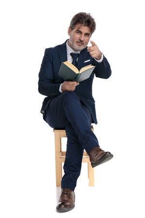 elegant formal business man with navy suit is sitting with legs crossed holding a book on one hand and pointing forward confident on white studio background