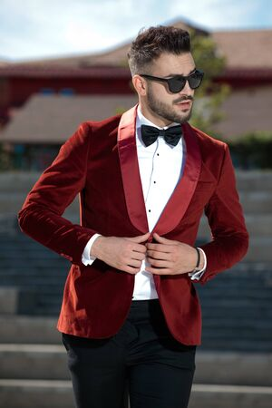seductive young man wearing red velvet tuxedo and sunglasses, holding hands and arranging coat, walking and looking to side, outdoor in an urban scene