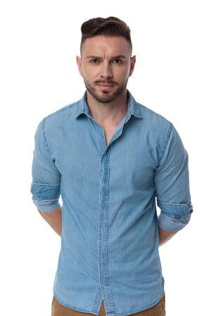 un bel homme décontracté avec une chemise bleue se tient les mains derrière lui mystérieux sur fond de studio blanc Banque d'images
