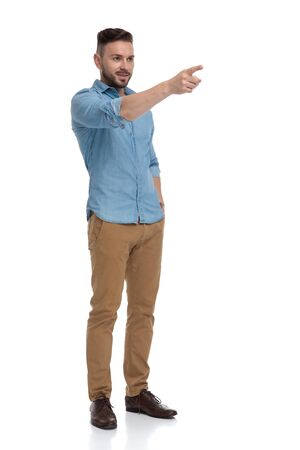 side view of a sexy casual man with blue shirt standing with hand in pocket and pointing forward serious on white studio background