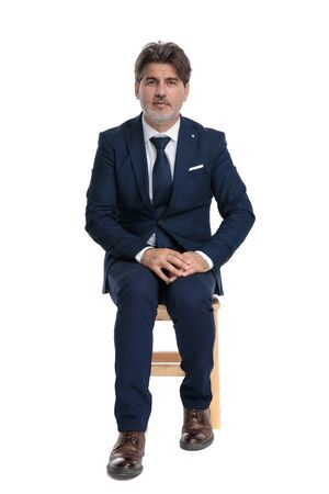 middle aged formal business man with navy suit is sitting and looking at camera holding hands serious on white studio background 스톡 콘텐츠