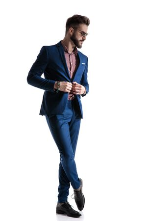 Wunderschöner formeller Geschäftsmann im blauen Anzug mit Bart und Sonnenbrille steht mit gekreuzten Beinen und repariert seine Jacke, während er nachdenklich auf weißem Studiohintergrund schaut Standard-Bild