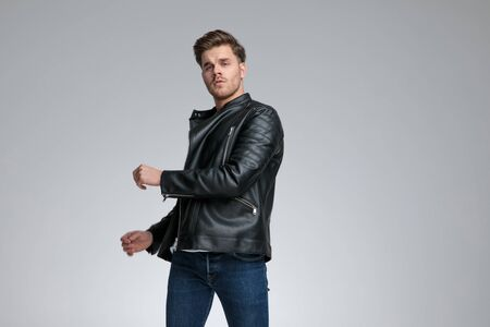 good looking casual man with black leather jacket is standing twisted with one hand over his body seductive on gray studio background Banco de Imagens