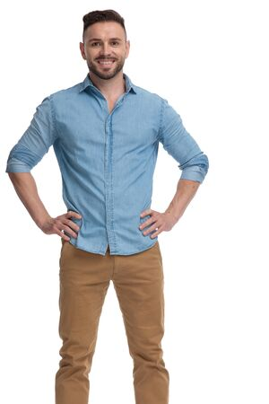 attractive casual man with blue shirt is standing with hands on waist and looking at camera confident on white studio background