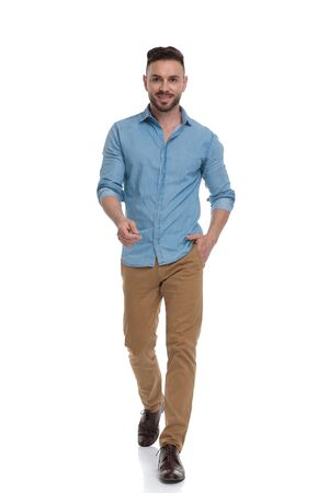 beautiful casual man with blue shirt walking with one hand in pocket and the other hand raised happy on white studio background