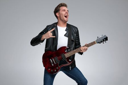 side view of a gorgeous casual man with black leather jacket standing and playing his guitar passionate with a rock sign gesture on gray studio background Stock Photo