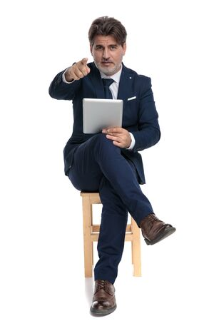 attractive formal business man with navy suit is sitting with legs crossed holding his tablet and pointing forward confident on white studio background