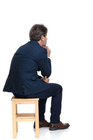 Vista trasera de un hombre de negocios formal con traje azul marino sentado y tocando su barbilla pensativo sobre fondo blanco de estudio