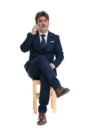 charming formal business man with navy suit is sitting with legs crossed and talking on the mobile phone confident on white studio background