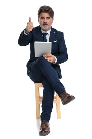 sexy formal business man with navy suit is sitting with crossed legs holding a tablet on one hand and a ok sign gesture confident on white studio background