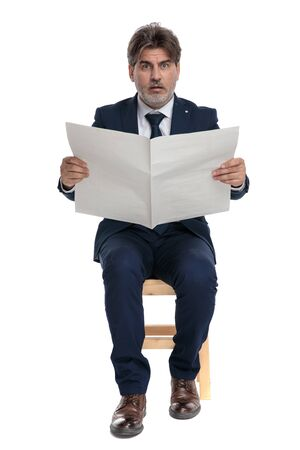 good looking formal business man with navy suit is sitting and holding a newspaper with big eyes shocked on white studio background Stockfoto - 130341265